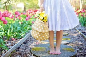 Woman in white dress holding a yellow and white polka dot bag with flowers