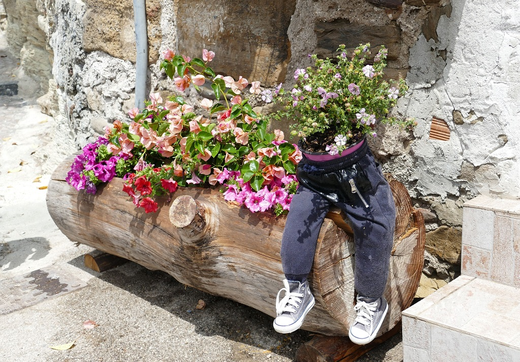 an old log planted with annuals and a fun stuffed person sitting on the log